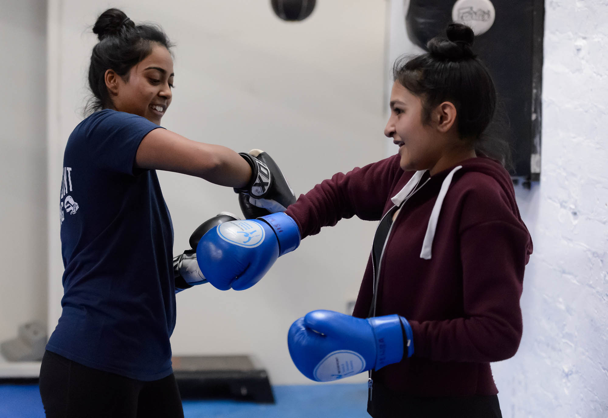 Two girls lacing up boxing gloves