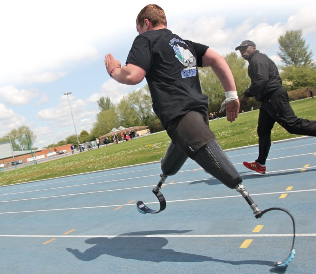 A double leg amputee being coached on the running track