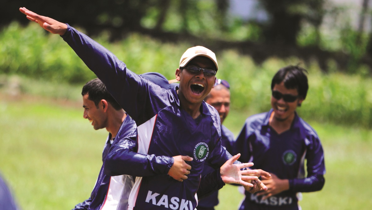 A blind bowler celebrates taking a wicket with team-mates