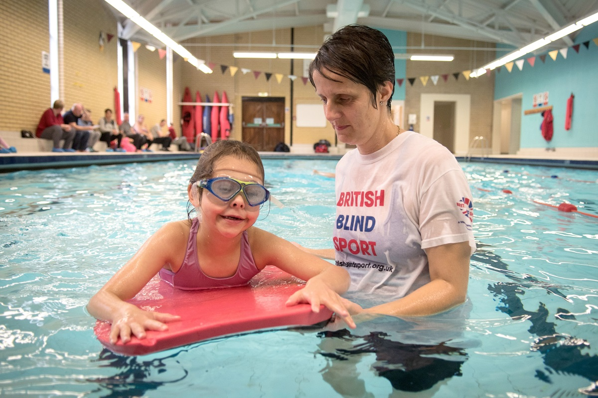 A blind child enjoys learning how to swim