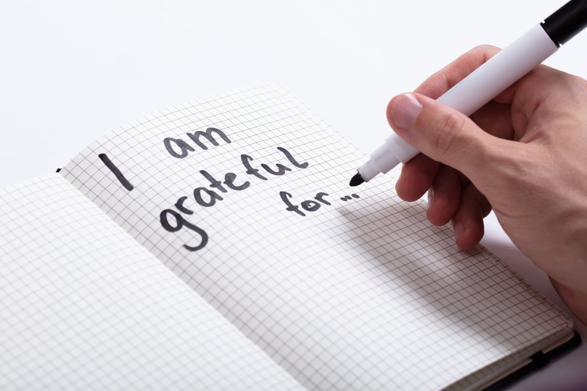 A person writes 'I am grateful for...' in black marker pen on a blank writing pad
