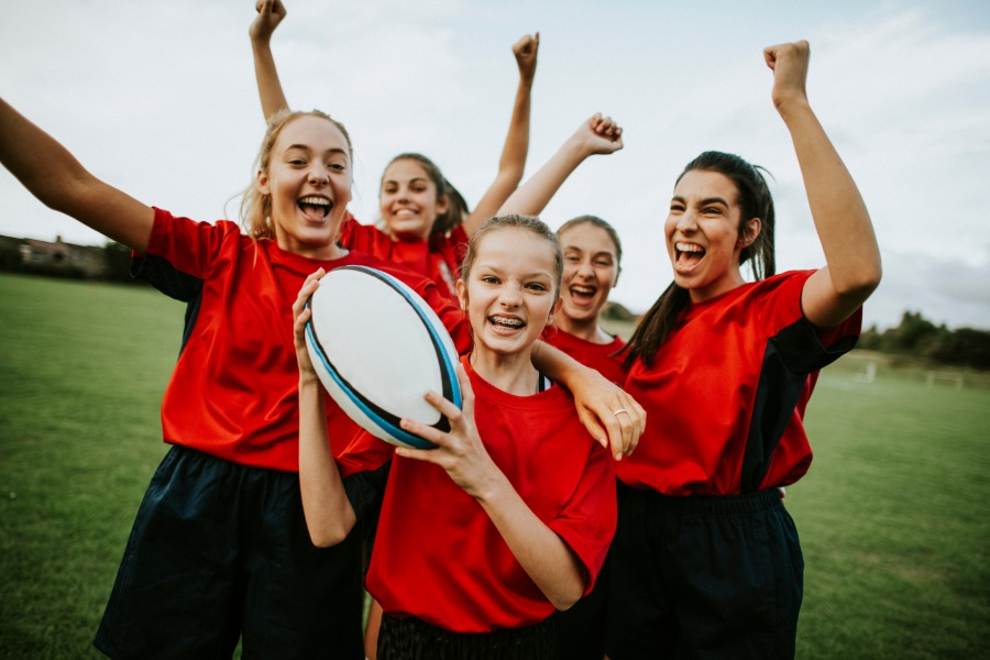 Group of smiling women, all cheering, one holding a rugby ball