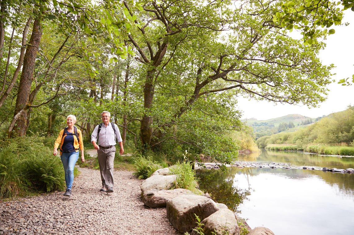 A couple walk alongside a river deep in the countryside