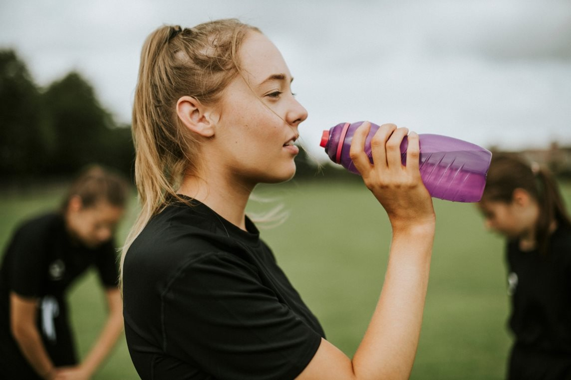 Young woman in sports gear on a field drinking from a water bottle
