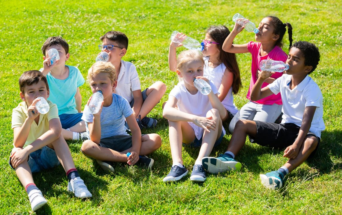 Young children drink from plastic water bottles after playing outdoor sport