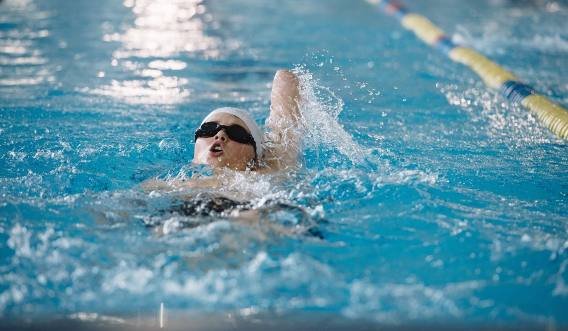 Young disabled swimmer who lacks an arm does the backstroke