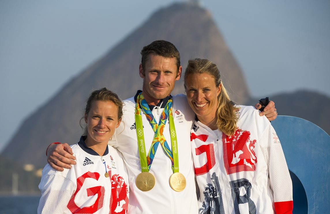 Hannah Mills (left) with coach Joe Glanfield (middle) wearing two gold medals, with Saskia Clark (right)